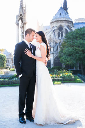Bride Embraces Groom in Front of Setting Sun at Notre Dame