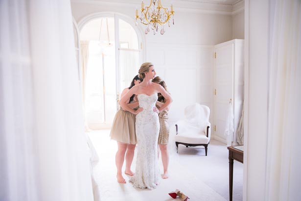 Bridesmaids Helping Bride with Dress in White Paris Hotel